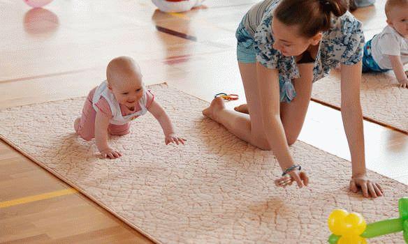 Мама показывает ребенку как ползать